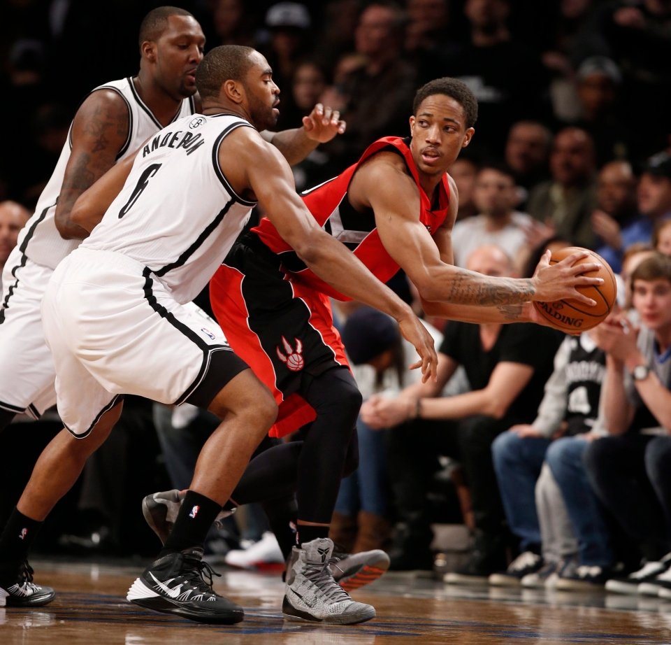 Toronto Raptors guard DeMar DeRozan (10) looks to pass as he is double teamed by Brooklyn Nets centre Andray Blatche, left, and Nets forward Alan Anderson (6) in the second half of Game 4 of an NBA basketball first-round playoff series at the Barclays Center in New York, Sunday, April 27, 2014. (AP / Kathy Willens)