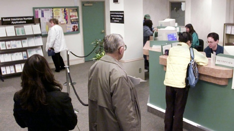 People stand in line waiting to speak to a receptionist at a Human Resources Centre in Vancouver, Friday, Jan. 11, 2002. (Chuck Stoody / THE CANADIAN PRESS)