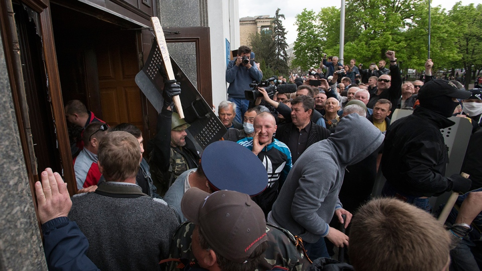A Pro-Russian activist waves a stick celebrating the capture of an administration building in the centre of Luhansk, Ukraine, Tuesday, April 29, 2014. (AP / Alexander Zemlianichenko)