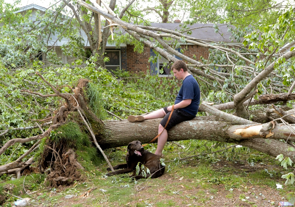 "Caleb Emerson and his dog ""Luke"" rest in front of his Seventh Ave. home in Athens, Ala., Tuesday, April 29, 2014. (The Decatur Daily / John Godbey)"
