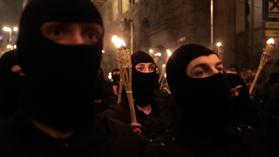 With their faces covered and carrying burning torches, Ukrainian nationalists attempt to march to Kyiv's Independence Square to honor the so called Heavenly Hundred, the protesters who were killed in clashes with police in February 2014, in Kyiv, Ukraine, Tuesday, April 29, 2014. (AP / Sergei Chuzavkov)