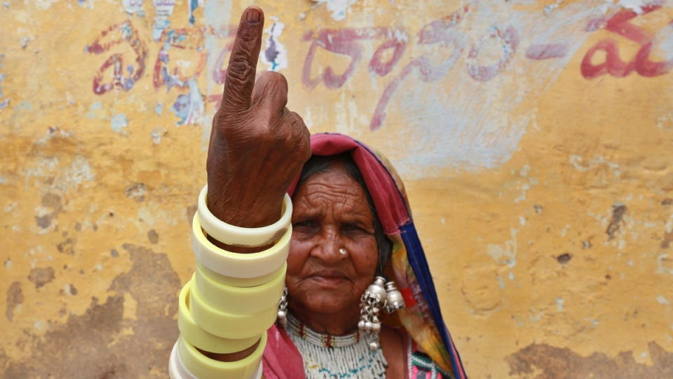 An Indian tribal woman displays the indelible ink mark on her finger after casting her vote at a polling station on the outskirts of Hyderabad, India, Wednesday, April 30, 2014. (AP / Mahesh Kumar A.)