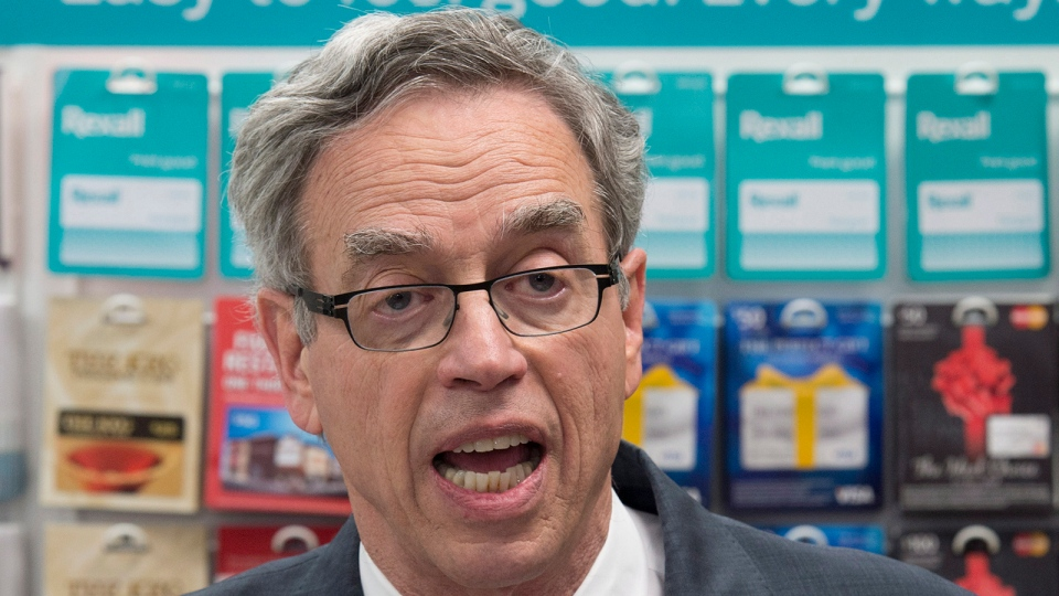 Standing in front of a gift card display Finance Minister Joe Oliver talks about the governments measures on prepaid cards, Wednesday April 30, 2014 in Ottawa. (Adrian Wyld / THE CANADIAN PRESS)