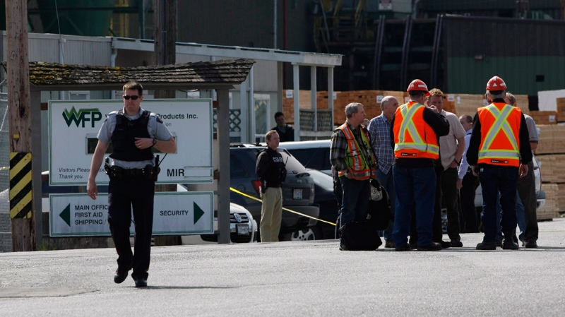 Mill workers talk following a shooting at Western Forest Products in Nanaimo, B.C., on Wednesday April 30, 2014. (THE CANADIAN PRESS/Chad Hipolito)