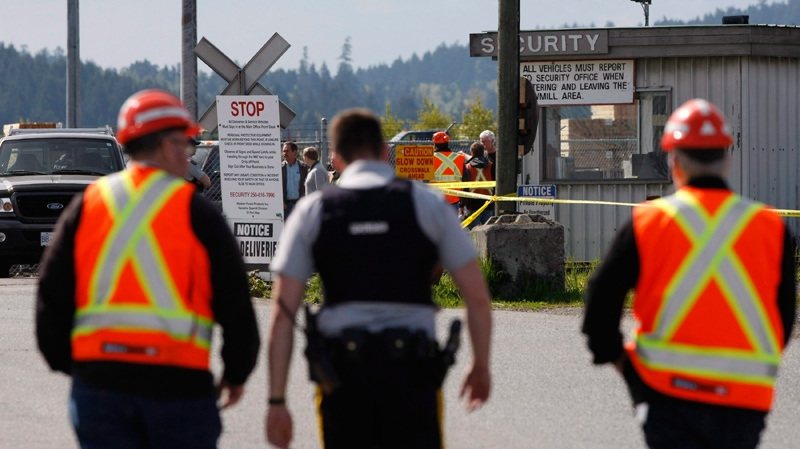 Mill workers and a police officer talk following a shooting at Western Forest Products in Nanaimo, B.C., on Wednesday April 30, 2014. (THE CANADIAN PRESS/Chad Hipolito)