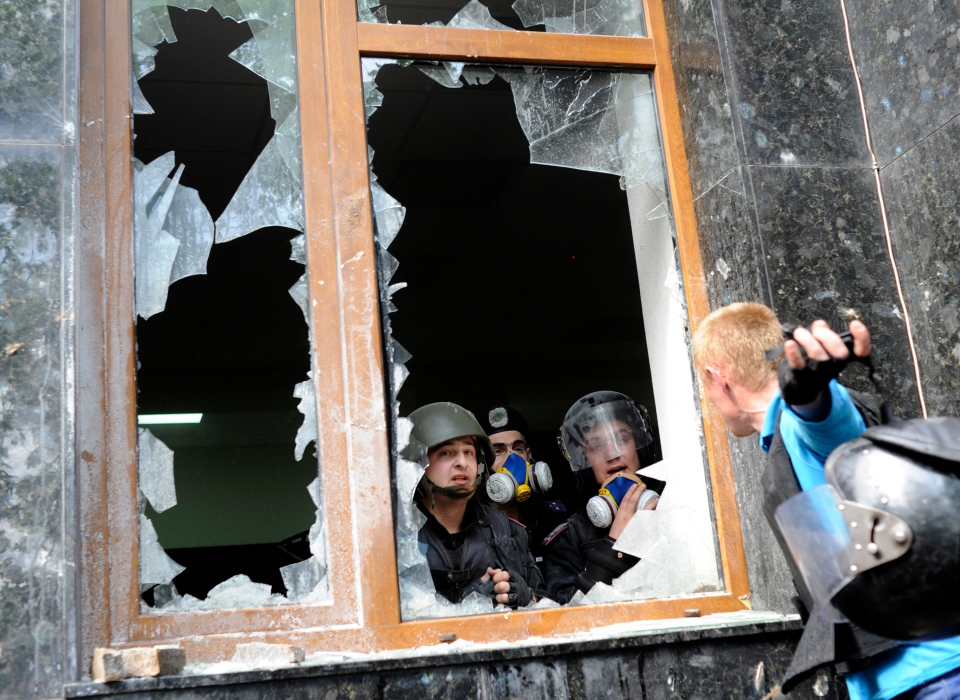 A Pro-Russian activist, right, speaks with police officers during clashes in front of the regional administration building in Donetsk, Ukraine, Thursday, May 1, 2014. (AP Photo/Evgeniy Maloletka)