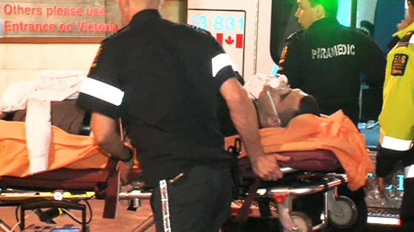 Paramedics are seen rushing a man to hospital following a shooting downtown Toronto early Sunday morning.