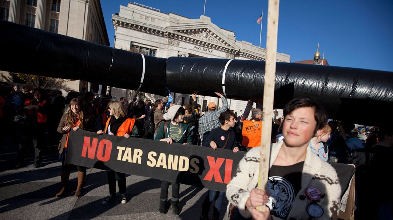 Demonstrators march with a replica of a pipeline during a protest to demand a stop to the Keystone XL tar sands oil pipeline outside the White House in Washington on Sunday, Nov. 6, 2011. (AP / Evan Vucci)