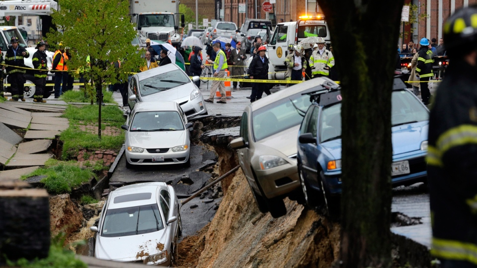 Cars sit on the edge of a sinkhole in the Charles Village neighborhood of Baltimore, Wednesday, April 30, 2014, as heavy rain moves through the region. (AP)