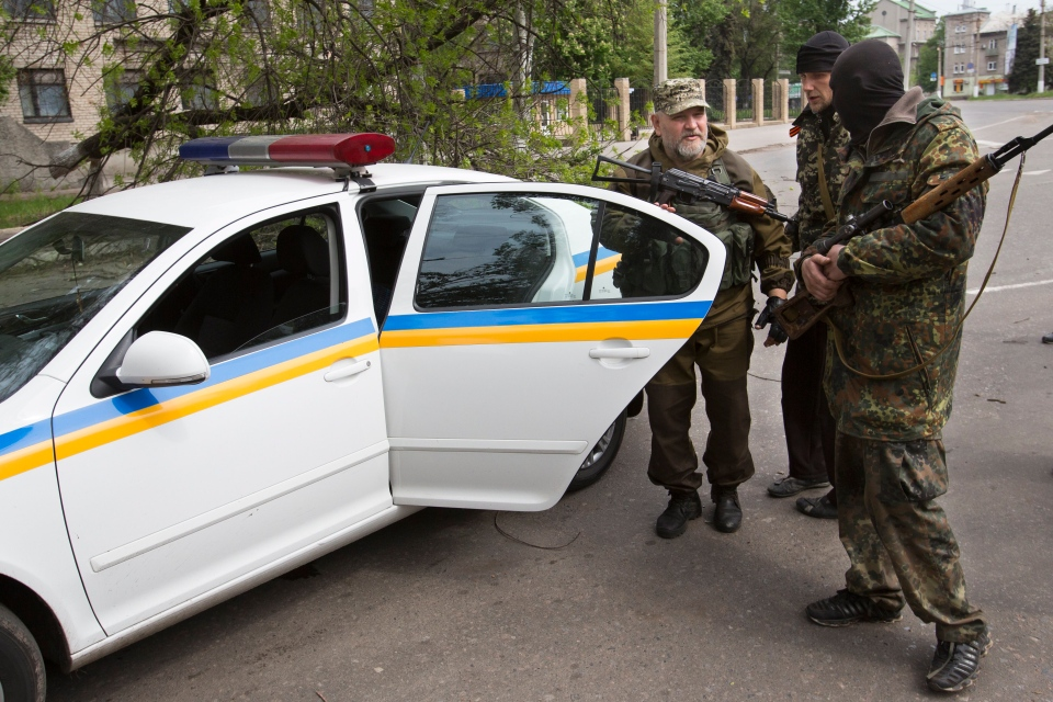 Pro-Russian gunmen listens to their commander, left, at a police car behind barricades in Slovyansk, eastern Ukraine, Friday, May 2, 2014. (AP / Alexander Zemlianichenko)