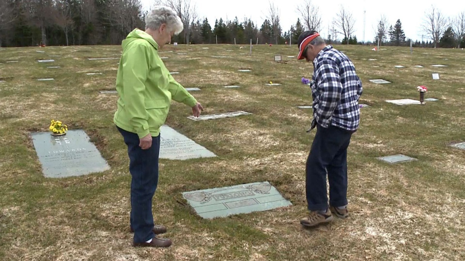 Elsie and Fred Furlong stand at their son's grave in Sydney Forks, N.S.
