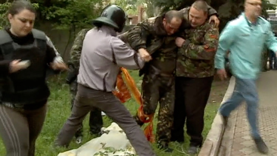 An injured Ukrainian military helicopter pilot is assisted by pro-Russian activists after he was shot down in Slovyansk, eastern Ukraine, Friday May 2, 2014. (Rossia 24 Television Channel)