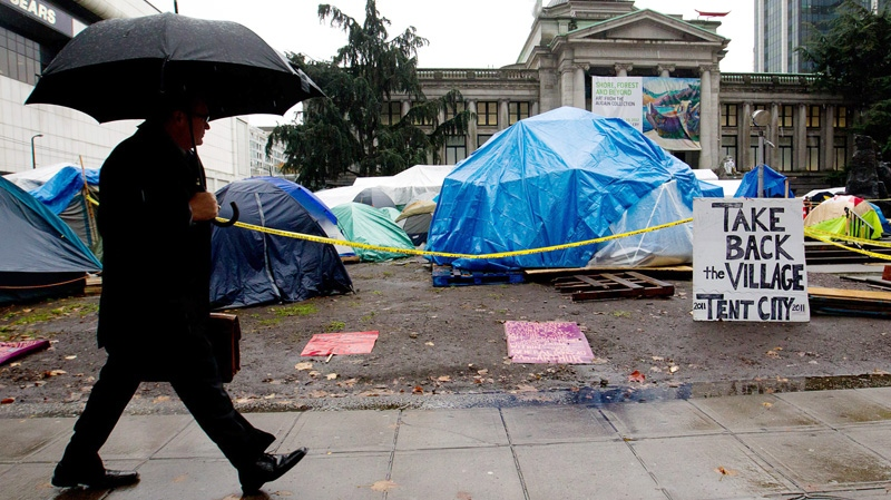 A businessman walks past the Occupy Vancouver site in downtown Vancouver, B.C., on Monday, Nov. 7, 2011. (Darryl Dyck / THE CANADIAN PRESS)
