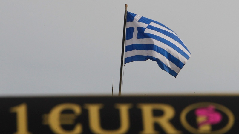 A Greek flag flies, as an advertising sticker on a mini van that delivers coffee products, displays the euro symbol in central Athens, Monday, Nov. 7, 2011. (AP / Thanassis Stavrakis)