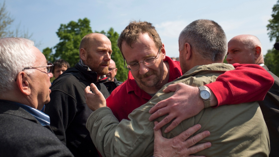 Russia's presidential human rights ombudsman Vladimir Lukin, left, and members of foreign military observers, German Col. Axel Schneider, second from left, watch other members hug at each other following their release in Slovyansk, eastern Ukraine, Saturday, May 3, 2014. (AP / Alexander Zemlianichenko)