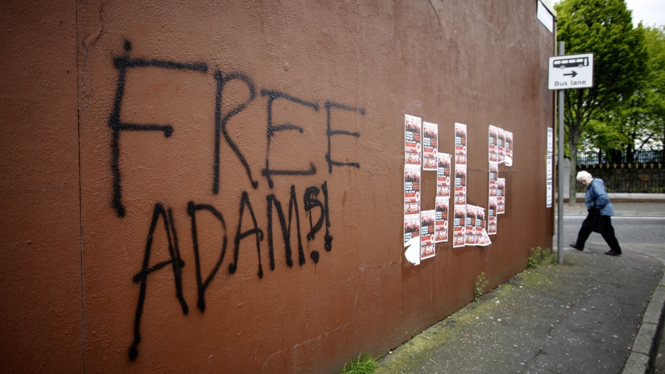 'Free Adams' is seen written on a wall on the Falls Road, West Belfast, Northern Ireland, Saturday, May, 3, 2014. (AP / Peter Morrison)