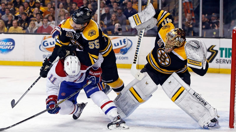 Boston Bruins defenseman Johnny Boychuk (55) checks Montreal Canadiens right wing Brendan Gallagher (11) as Bruins goalie Tuukka Rask (40) protects the net during the first period in Game 2 of an NHL hockey second-round playoff series in Boston, Saturday, May 3, 2014. (AP Photo/Elise Amendola)