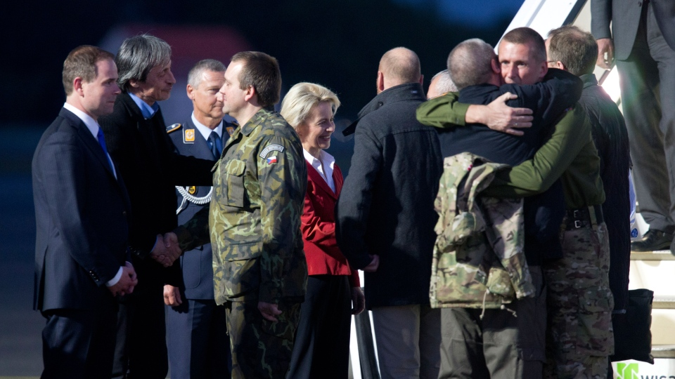 Denmark's minister for defense Nicolai Waamen, left, Czech Defence Minister Martin Stropnicky, 2nd left, and German Defense Minister Ursula von der Leyen, center in red, welcomes the released OSCE observers in Berlin, Germany, Saturday May 3, 2014. (AP / Axel Schmidt)