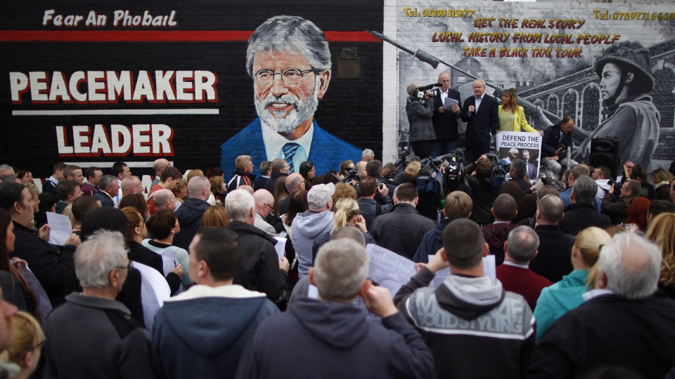 Sinn Fein's Martin McGuinness, centre, with party members Bobby Storey, left, and Martina Anderson speak during a protest rally on the Falls Road, West Belfast, Northern Ireland, Saturday, May, 3, 2014. (AP / Peter Morrison)