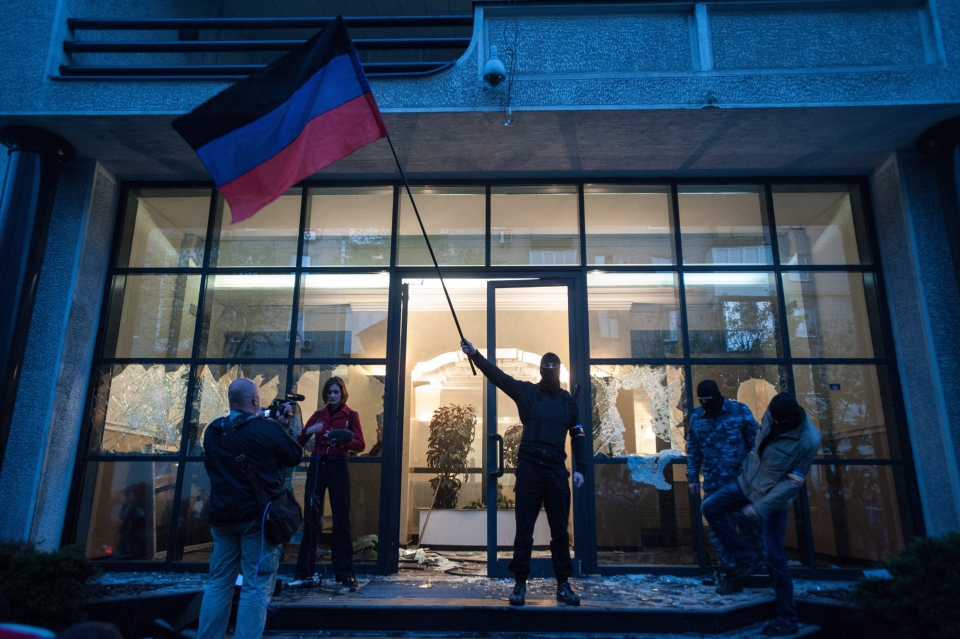 Pro-Russian activist waves a Donetsk republic flag in front of the offices of Industrial Union of Donbass Corporation in Donetsk, eastern Ukraine on Saturday, May 3, 2014. (AP / Evgeniy Maloletka)