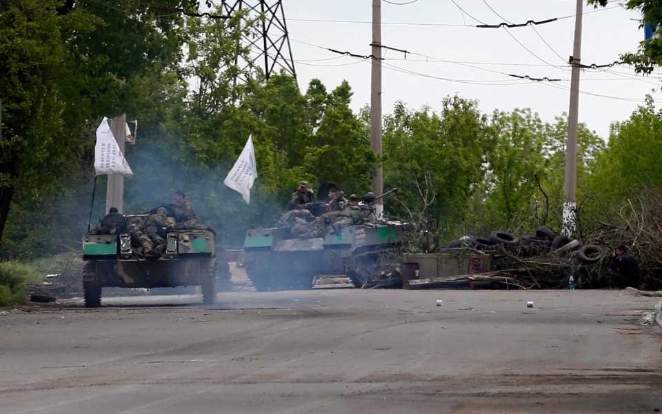 Pro-Russian gunmen atop armored personal carriers passing by barricades on a road leading into Slovyansk, eastern Ukraine, Monday, May 5, 2014. (AP / Darko Vojinovic)