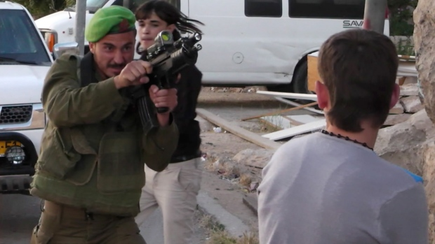 Israeli soldier confronts a Palestinian teen
