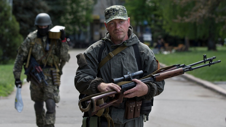 Pro-Russian gunmen carry their weapons at the local administration building in the centre of Slovyansk, Ukraine, Tuesday, May 6, 2014. (AP / Alexander Zemlianichenko)
