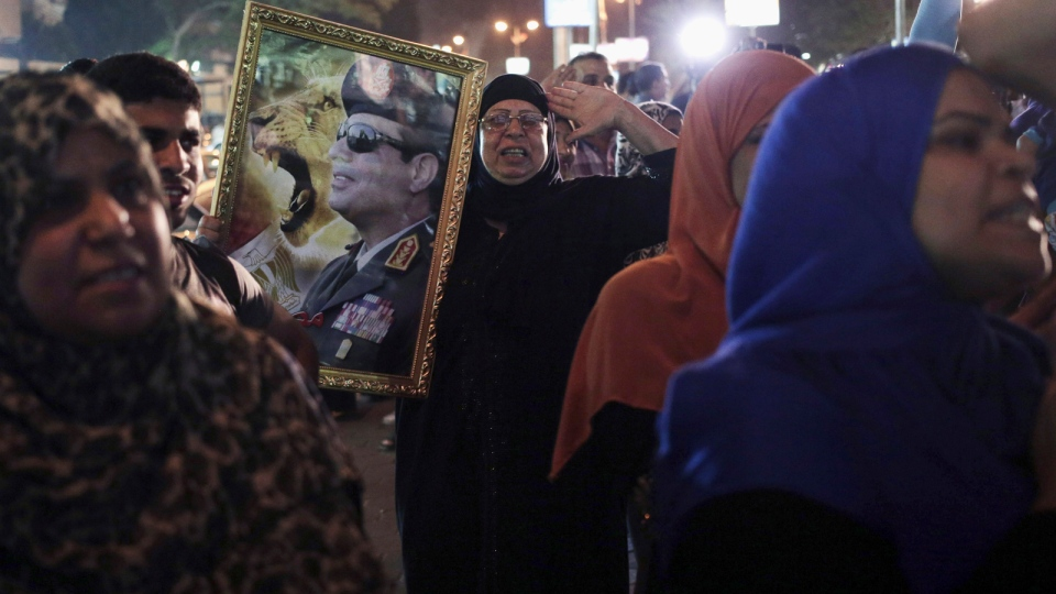 Supporters of Egypt's former army chief Abdel-Fattah el-Sissi gather to watch his first televised interview shown on a big screen in the street in downtown Cairo, Egypt, Monday, May 5, 2014. (AP / Khalil Hamra)