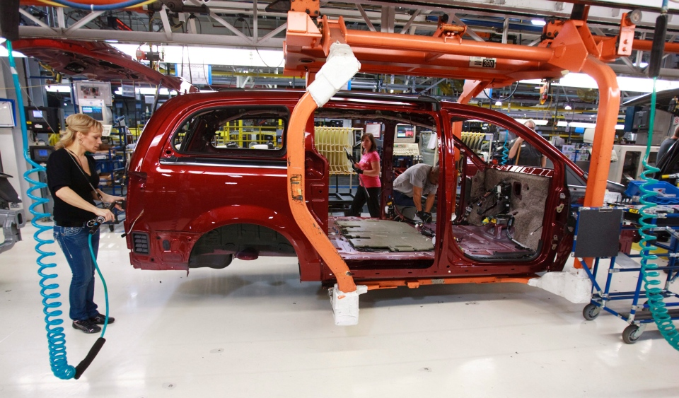 A worker on the production line at Chrysler's assembly plant in Windsor, Ontario, works on one of their new minivans on Tuesday, January 18, 2011. (GEOFF ROBINS / The Canadian Press)