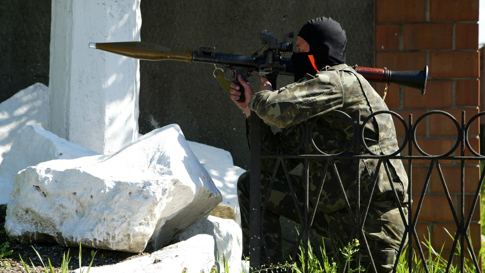 A pro-Russian militant aims his weapon as a group of gunmen try to block a military base of Ukrainian riot police in Donetsk, Ukraine, Tuesday, May 6, 2014. (AP  /Alexander Ermochenko)