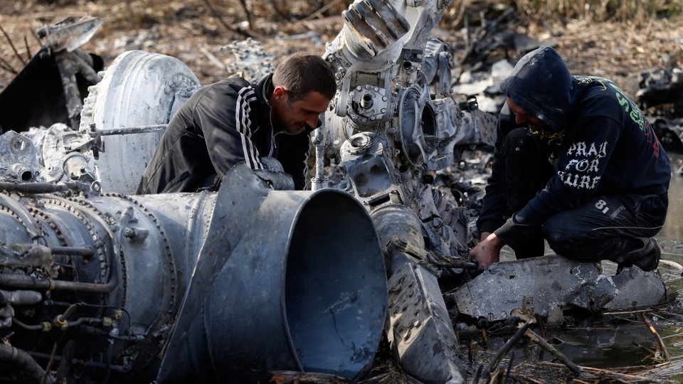 Local citizens collect parts of a downed Ukrainian military helicopter near a small town Raigorodok, outside Slovyansk, Ukraine, Tuesday, May 6, 2014. (AP / Darko Vojinovic)