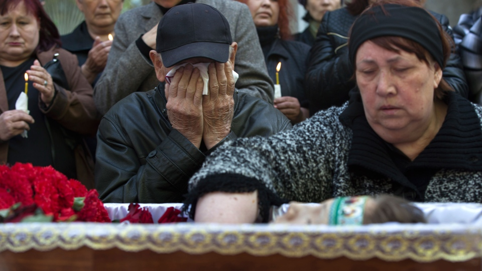 Relatives cry around the coffin of 17 year-old Vadim Papura during a religious service outside his apartment block, in Odessa, Ukraine, Tuesday May 6, 2014. (AP / Vadim Ghirda)