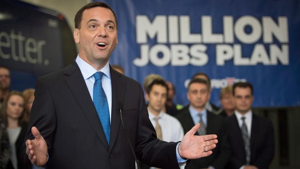 Ontario PC Leader Tim Hudak speaks to reporters in front of a group of PC candidates and Pacific Western Transportation employees during a press conference in Mississauga, Ont. on Wednesday, May 7, 2014. (THE CANADIAN PRESS / Darren Calabrese)