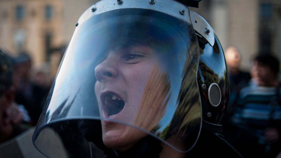 A pro-Russian activist wearing police helmet shouts outside the regional interior ministry building in Luhansk, eastern Ukraine, Wednesday, May 7, 2014. (AP / Evgeniy Maloletka)