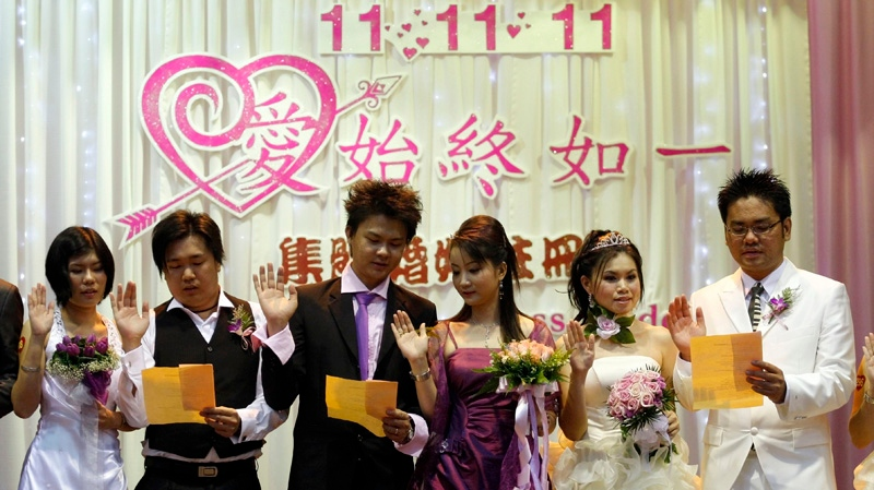 Newlywed couples swear in during a mass wedding ceremony at the Hokkien Association building in Klang, outside Kuala Lumpur, Malaysia, Friday, Nov. 11, 2011. Over 300 brides and grooms attended the ceremony to mark the unique date of 11-11-11.