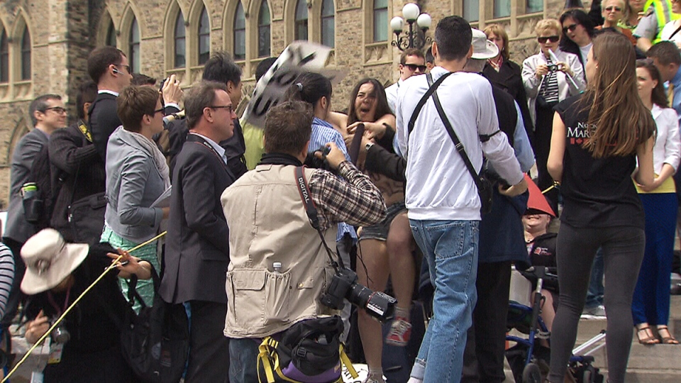 A pro-choice protester is removed by RCMP officers at the 'March For Life' on Parliament Hill in Ottawa on Thursday, May 8, 2014.