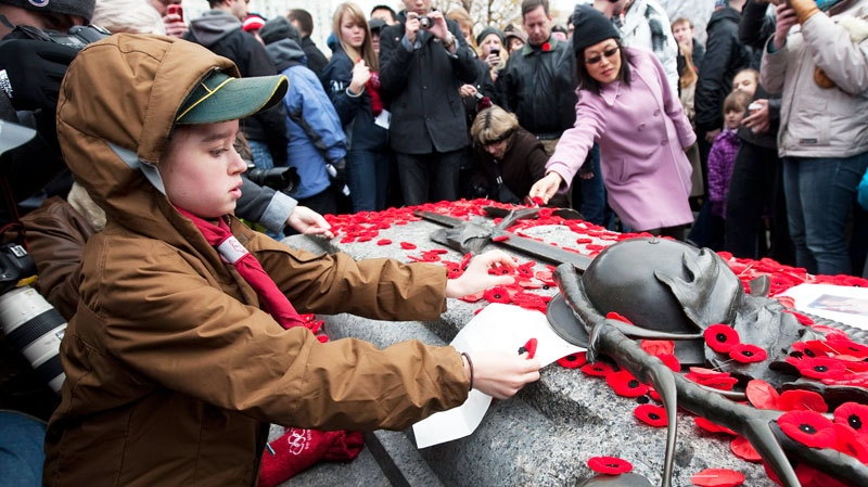 A young boy places a letter on the Tomb of the Unknown Soldier following Remembrance Day ceremonies at the National War Memorial in Ottawa Friday November 11, 2011. (Adrian Wyld / THE CANADIAN PRESS)