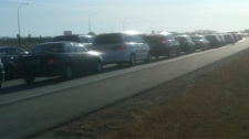 A lineup of vehicles headed to the U.S. is shown near Emerson, Man. on Nov. 11, 2011.