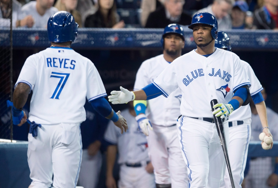 Toronto Blue Jays' Edwin Encarnacion, right, and Jose Reyes celebrate after Reyes scored in the third inning of MLB baseball action against the Philadelphia Phillies in Toronto on Thursday, May 8, 2014. THE CANADIAN PRESS/Darren Calabrese