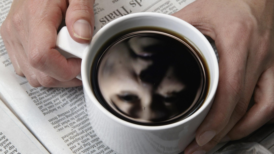 A woman looks into a cup of coffee in Toronto on Monday Jan. 10, 2004. (CP / Frank Gunn)
