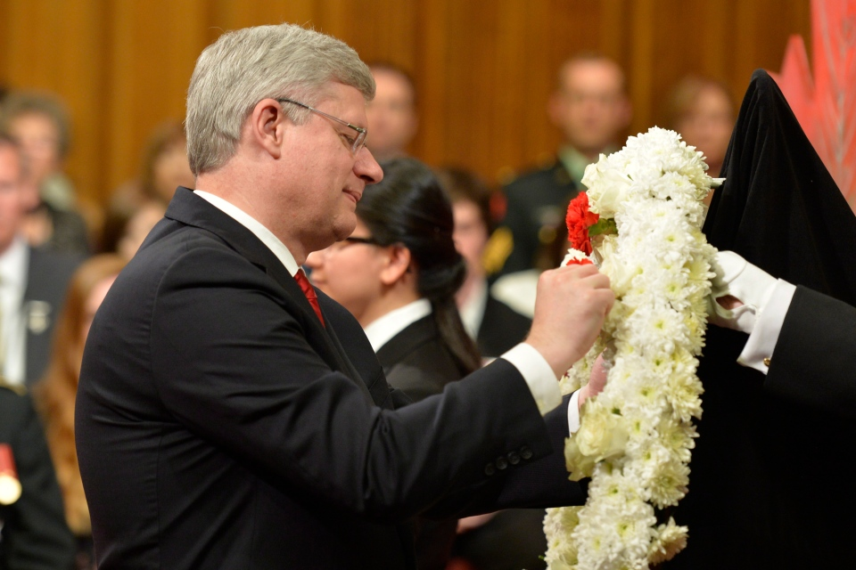 Prime Minister Stephen Harper places a flower on a wreath at a National Day of Honour ceremony in Ottawa,  Friday, May 9, 2014. (Adrian Wyld / THE CANADIAN PRESS)