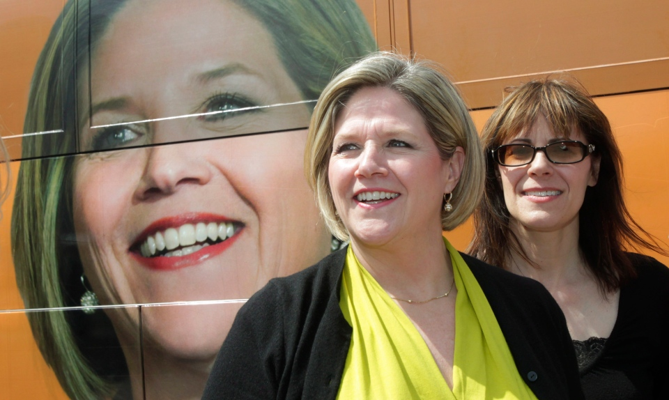 Ontario NDP leader Andrea Horwath stands next to her campaign bus with London-Fanshawe MPP Teresa Armstrong while campaigning in downtown London, Ont., Thursday, May 8, 2014. (Dave Chidley / THE CANADIAN PRESS)