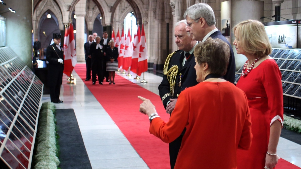 Governor General David Johnston and Prime Minister Stephen Harper along with their wives Laureen Harper and Sharon Johnston view plaques plaques in the Hall of Honour, honouring the Canadian soldiers killed during the Afgahistan conflict, during ceremonies for Canada's National Day of Honour on Parliament Hill on Friday May 9, 2014. (Fred Chartrand / THE CANADIAN PRESS)