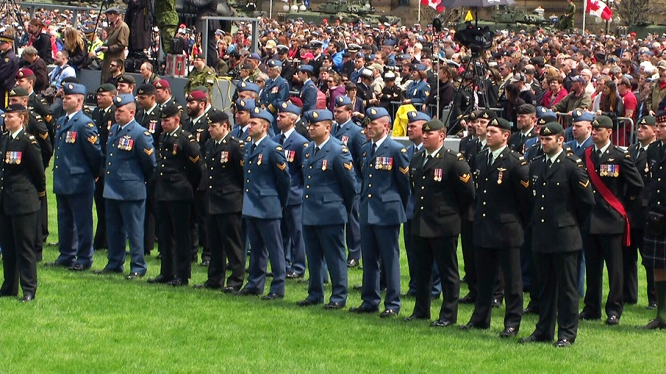 Members of the Canadian Forces stand in front of a crowd gathered to pay respects to the veterans and the dead of the Afghanistan war, on Parliament Hill in Ottawa, Friday, May 9, 2014.