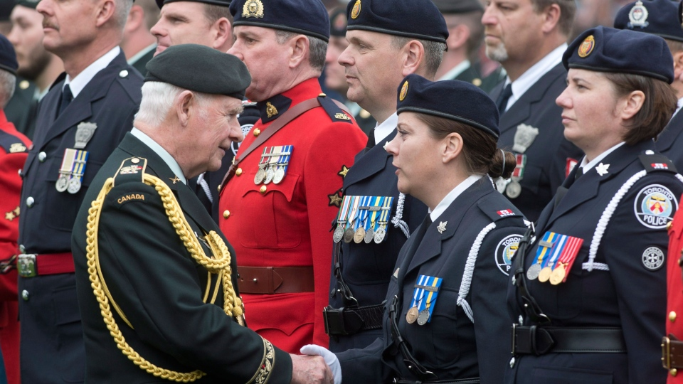 Governor General David Johnston shakes hands with police officers who served in Afghanistan during a National Day of Honour as he inspects the guard in Ottawa on Friday May 9, 2014. (Adrian Wyld / THE CANADIAN PRESS)