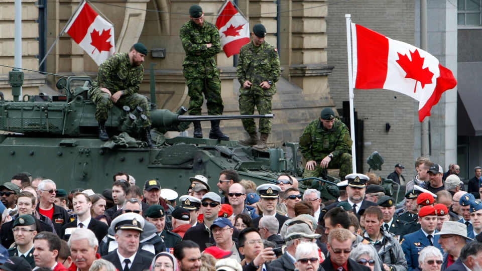 Soldiers stand on military armoured vehicles as people gather on Parliament Hiil in Ottawa during ceremonies for Canada's National Day of Honour, Friday, May 9, 2014. (Fred Chartrand / THE CANADIAN PRESS)