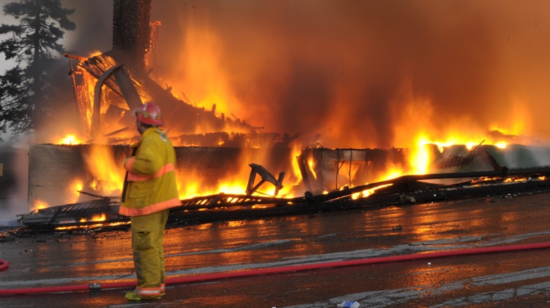 A firefighter looks on as White Point Beach Resort's main lodge burns in the background on Saturday Nov. 12, 2011.