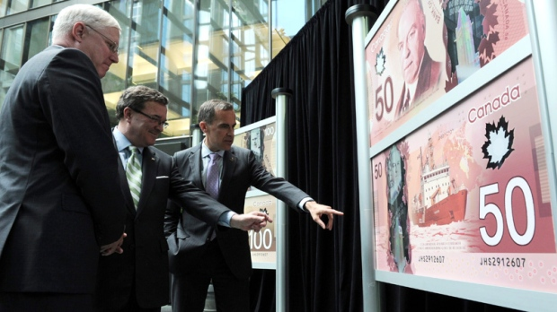 Bank of Canada Governor Mark Carney, right, Finance Minister Jim Flaherty, centre, and RCMP Commissioner William Elliott unveil the new polymer bank notes in $50 and $100 denominations at the Bank of Canada in Ottawa on Monday, June 20, 2011. (Sean Kilpatrick / THE CANADIAN PRESS)