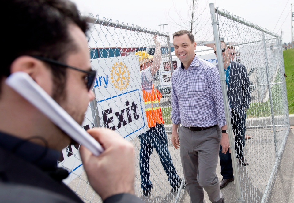 Security waits as Ontario PC Leader Tim Hudak leaves a food truck festival during a campaign stop in Whitby, Ont. on Saturday, May 10, 2014. (Darren Calabrese / THE CANADIAN PRESS)