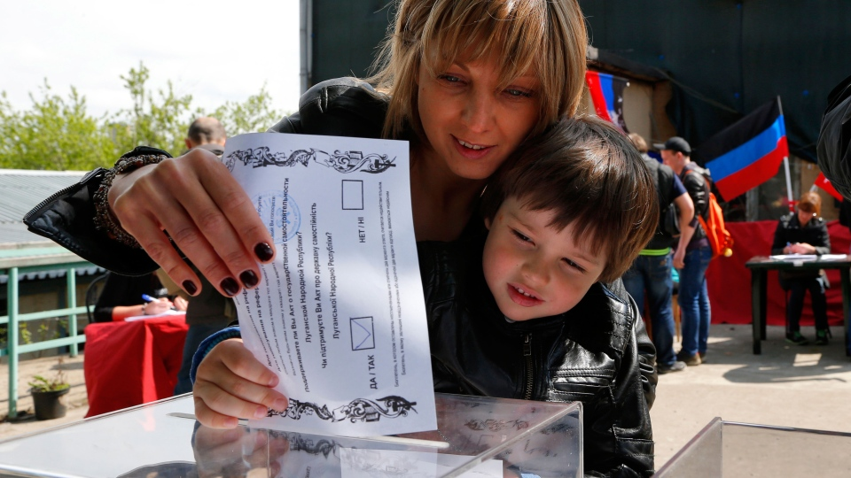 An Ukrainian woman and her son, who are in Russia at the moment, cast a referendum ballot in Moscow, Russia, on Sunday, May 11, 2014. (AP / Dmitry Lovetsky)